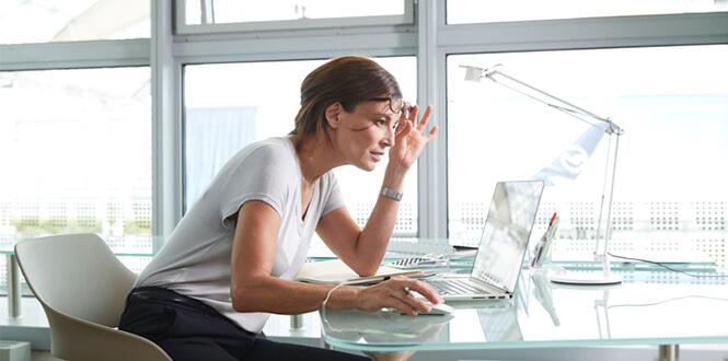 Frau am Schreibtisch mit Brille Linsenimplantation